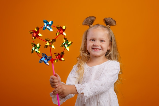 Little girl holding a toy windmill on a yellow space