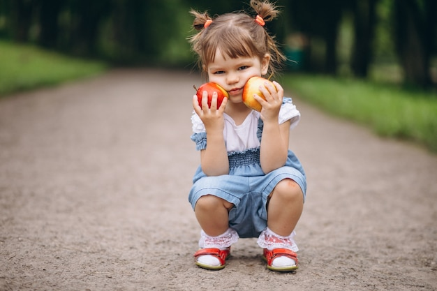 Little girl holding two apples