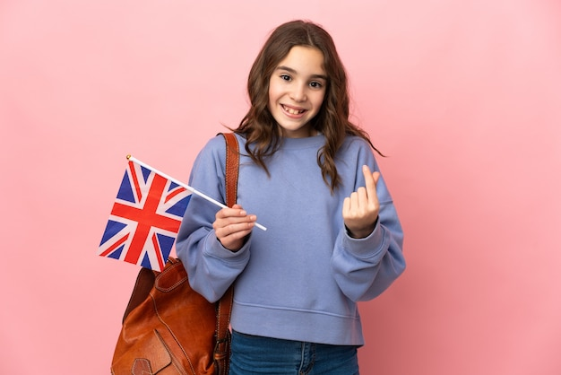 Little girl holding an united kingdom flag isolated on pink background making money gesture