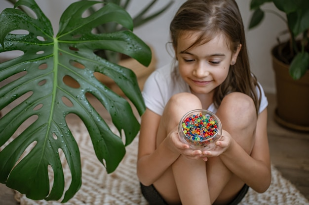 Little girl holding a vase with decorative multicolored water beads.