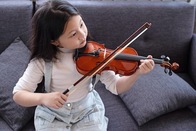 Little girl holding violin in hand