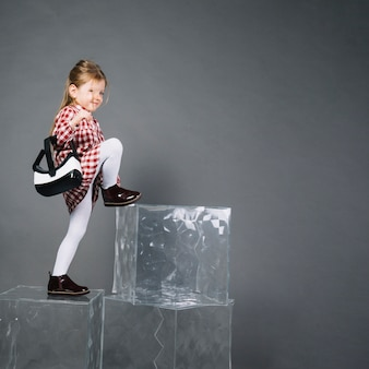 Little girl holding virtual reality glasses climbing on transparent blocks against gray background