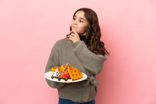 Маленькая девочка держит вафли на розовом фоне и смотрит вверх