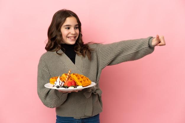 Маленькая девочка держит вафли, изолированные на розовом фоне, показывает палец вверх