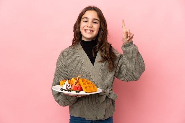Маленькая девочка держит вафли на розовом фоне, указывая на отличную идею