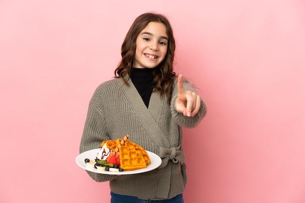 Маленькая девочка держит вафли на розовом фоне, показывая и поднимая палец