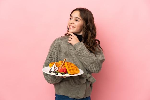 Маленькая девочка держит вафли, изолированные на розовой стене, глядя вверх, улыбаясь