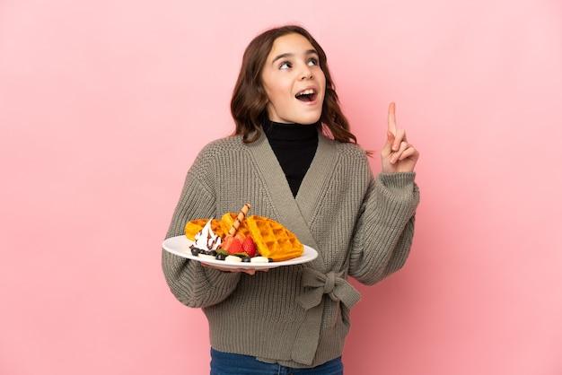 Маленькая девочка держит вафли, изолированные на розовой стене, думая об идее, указывая пальцем вверх