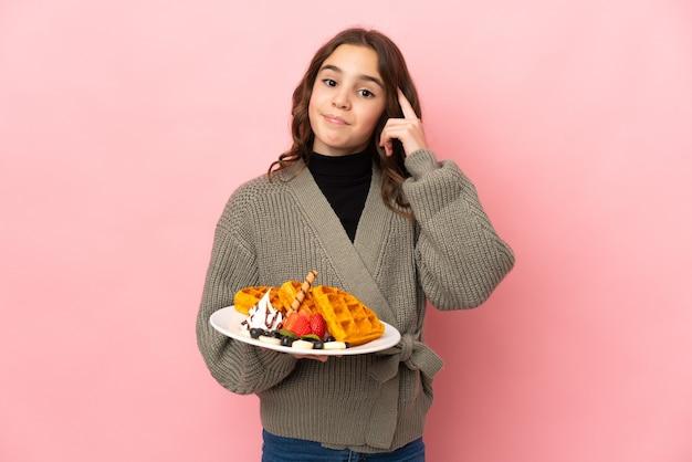Маленькая девочка держит вафли, изолированные на розовой стене, думая об идее