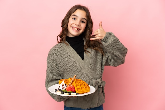 Little girl holding waffles isolated on pink wall making phone gesture. call me back sign