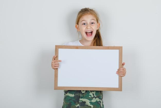 白いtシャツでホワイトボードを保持している小さな女の子