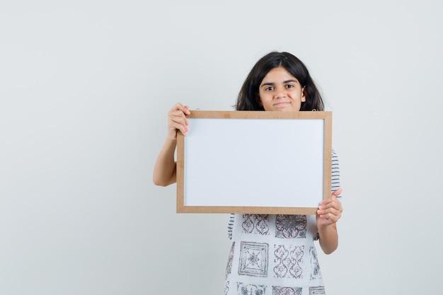 Bambina che tiene cornice bianca in t-shirt, grembiule e guardando fiducioso,