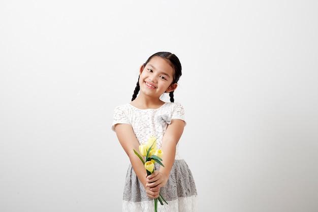 Little girl holding yellow tulips on white