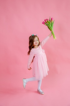 小さな女の子はピンクの背景にチューリップの花束を持っています
