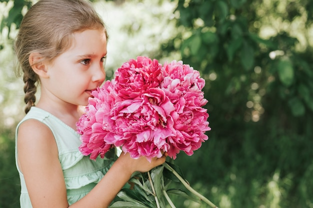 小さな女の子は彼女の手にピンクの花の花束を持って、それをかぐ