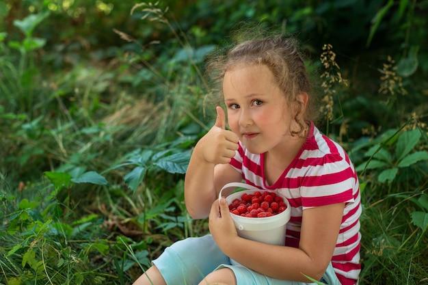 小さな女の子は赤いラズベリーとプラスチックのバケツを持っています