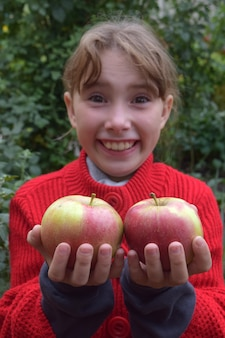 The little girl holds an apple . girl with an apple on a nature