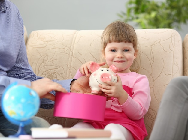 Little girl holds in arms piggy bank with plans for future