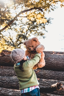 Little girl holds a bear in her arms on the background of logs on an autumn day.