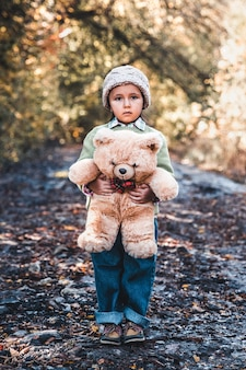 Little girl holds a bear in her arms on the background of nature on an autumn day.