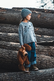Little girl holds a bear in her arms on wooden logs