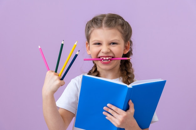 A little girl holds a book and colorful pencils in her hand and mouth on purple background