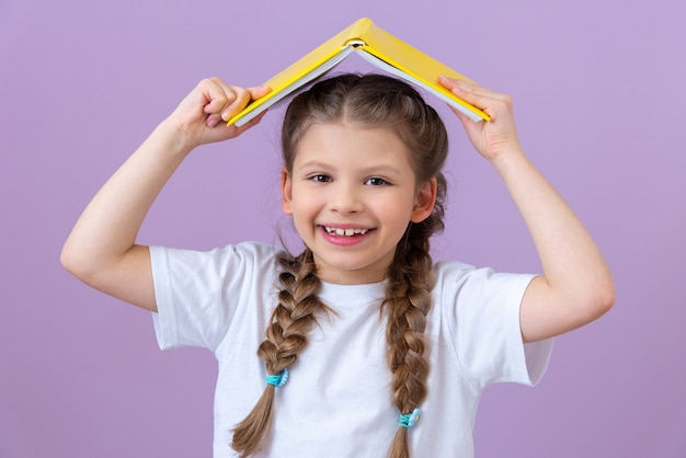 A little girl holds a book like a roof over her head on a purple background