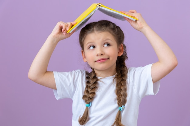 A little girl holds a book like a roof over her head.