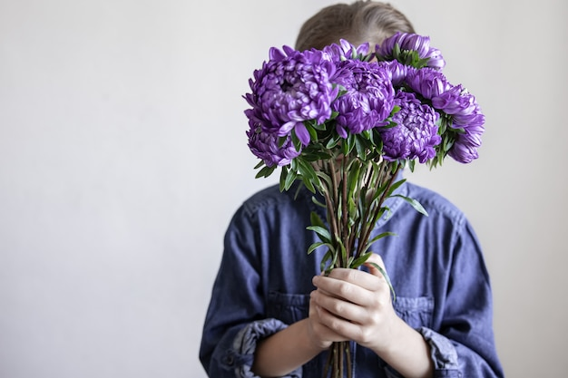 A little girl holds a bouquet of blue chrysanthemums in her hands, copy space.