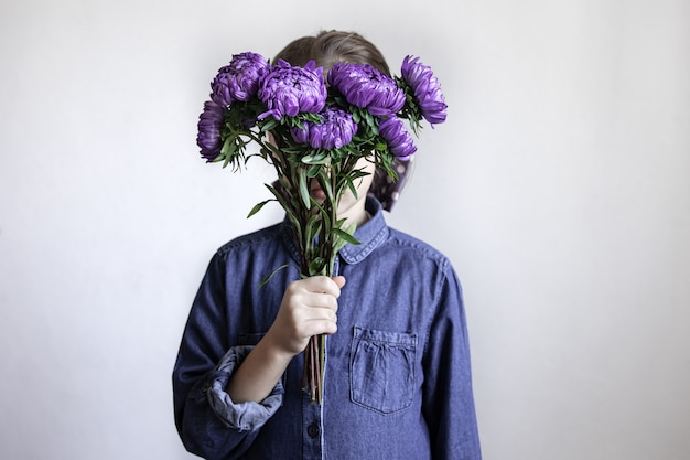 A little girl holds a bouquet of blue chrysanthemums in her hands.