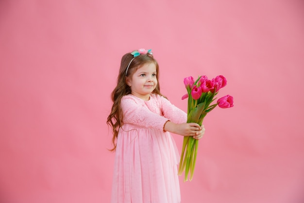 Little girl holds a bouquet of tulips on a pink background