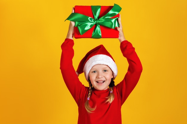 Little girl holds a box with a christmas present over her head.