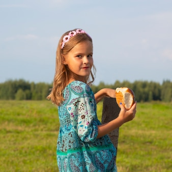 A little girl holds bread in her hand in a meadow in summer. baking, bread in the girl's hand