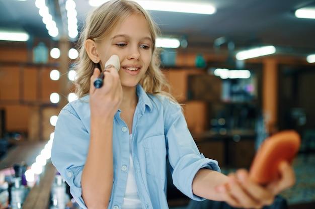 어린 소녀 메이크업 살롱에서 거울에 브러시를 보유