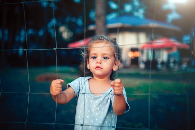 The little girl holds on to the fence with both hands and looks into the camera through the grid