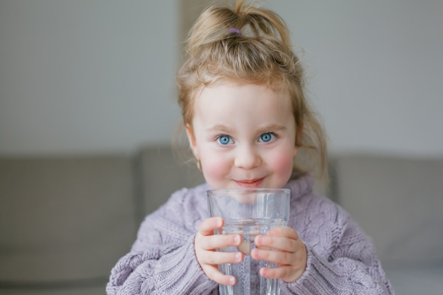 A little girl holds a glass of water, drinks. cozy.
