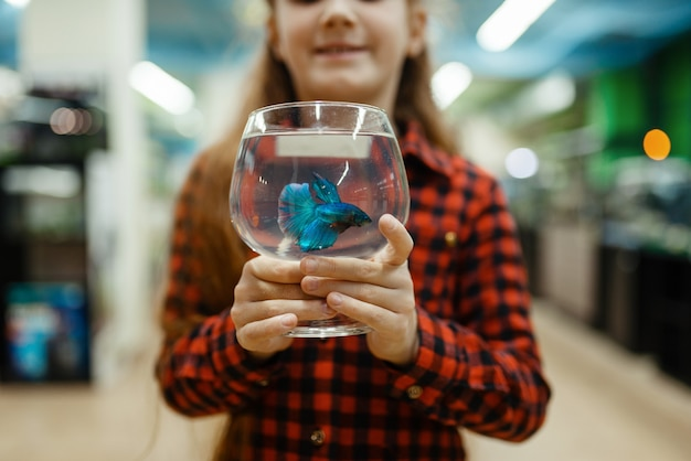 小さな女の子は、ペット ショップの青い魚の入ったガラスを持っています。ペットショップで子供を買う道具、家畜のアクセサリー