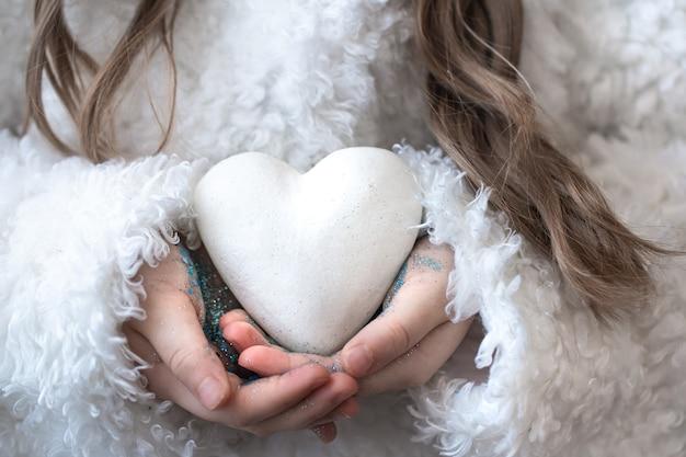 Una bambina tiene un cuore nelle sue mani.