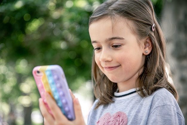 A little girl holds in her hand a phone in a case with pimples pop it, a trendy anti stress toy.