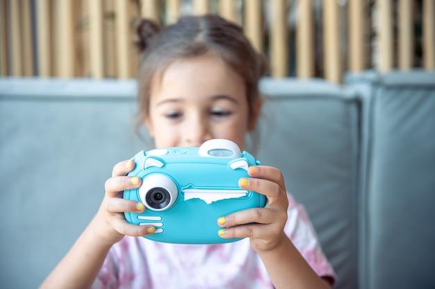 Una bambina tiene tra le mani una fotocamera digitale giocattolo blu per bambini per la stampa di foto istantanea.