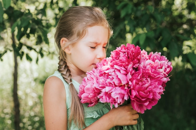 Little girl holds in her hands and smells a pink blouquet of flowers with her eyes closed