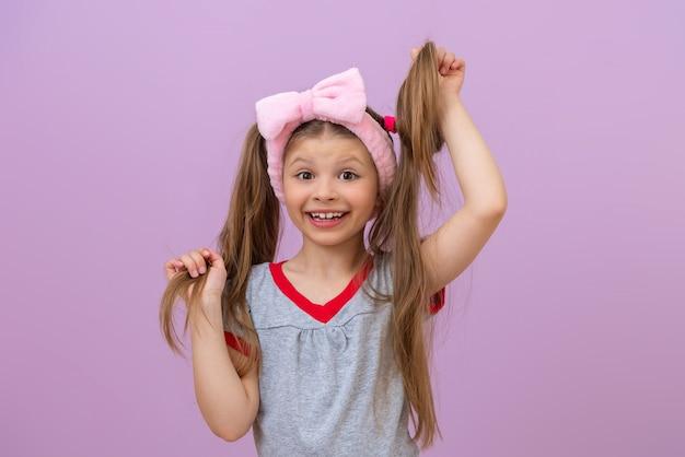 어린 소녀는 밝은 자주색 배경에 그녀의 손에 그녀의 묶은 머리를 보유하고 있습니다.