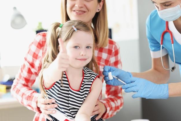 어린 소녀는 그녀의 엄지 손가락을 들고 의사는 메디나 사무실에서 그녀의 어깨를 예방 접종합니다.