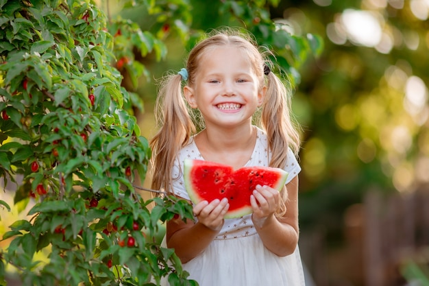 A little girl holds a piece of watermelon in the summer sun