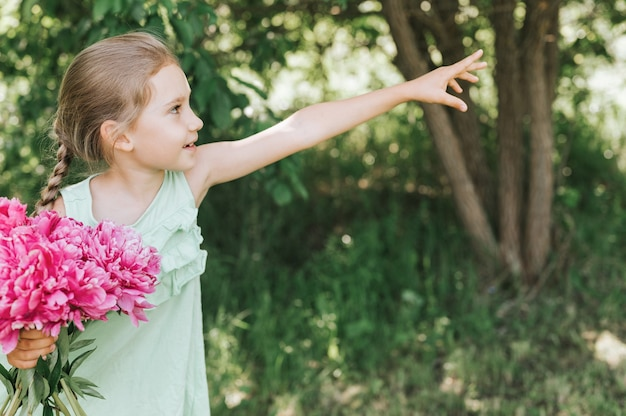 Little girl holds a pink flowers bouquet in hands and points to the side