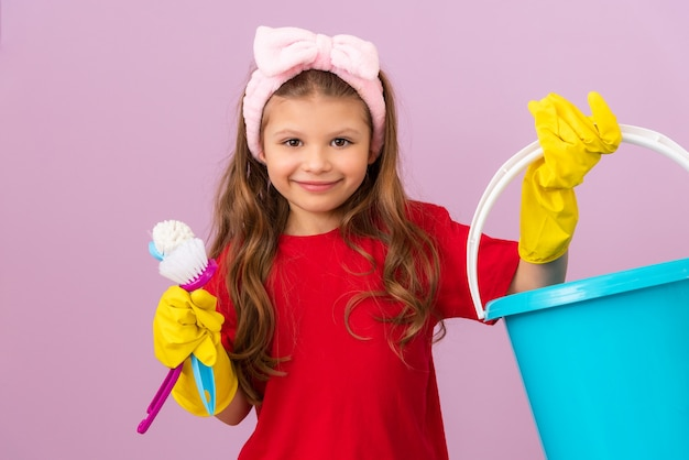 A little girl holds a plastic bucket and brushes for cleaning the room.