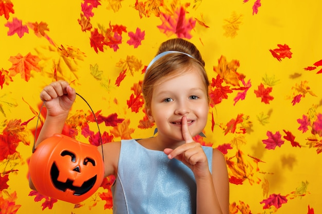 Little girl holds a pumpkin jack bucket and shows a shh sign.