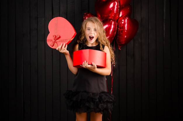 A little girl holds a red gift box in the shape of a heart smiling against a black background.