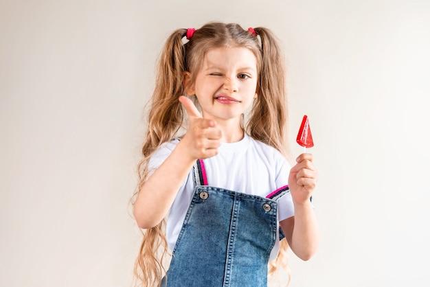 A little girl holds a red lollipop.