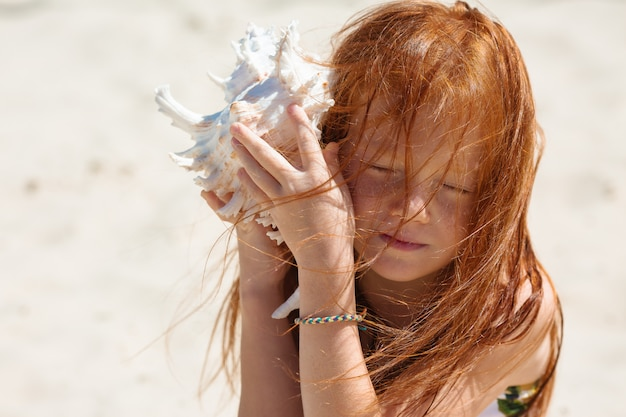Little girl holds a seashell near her ear
